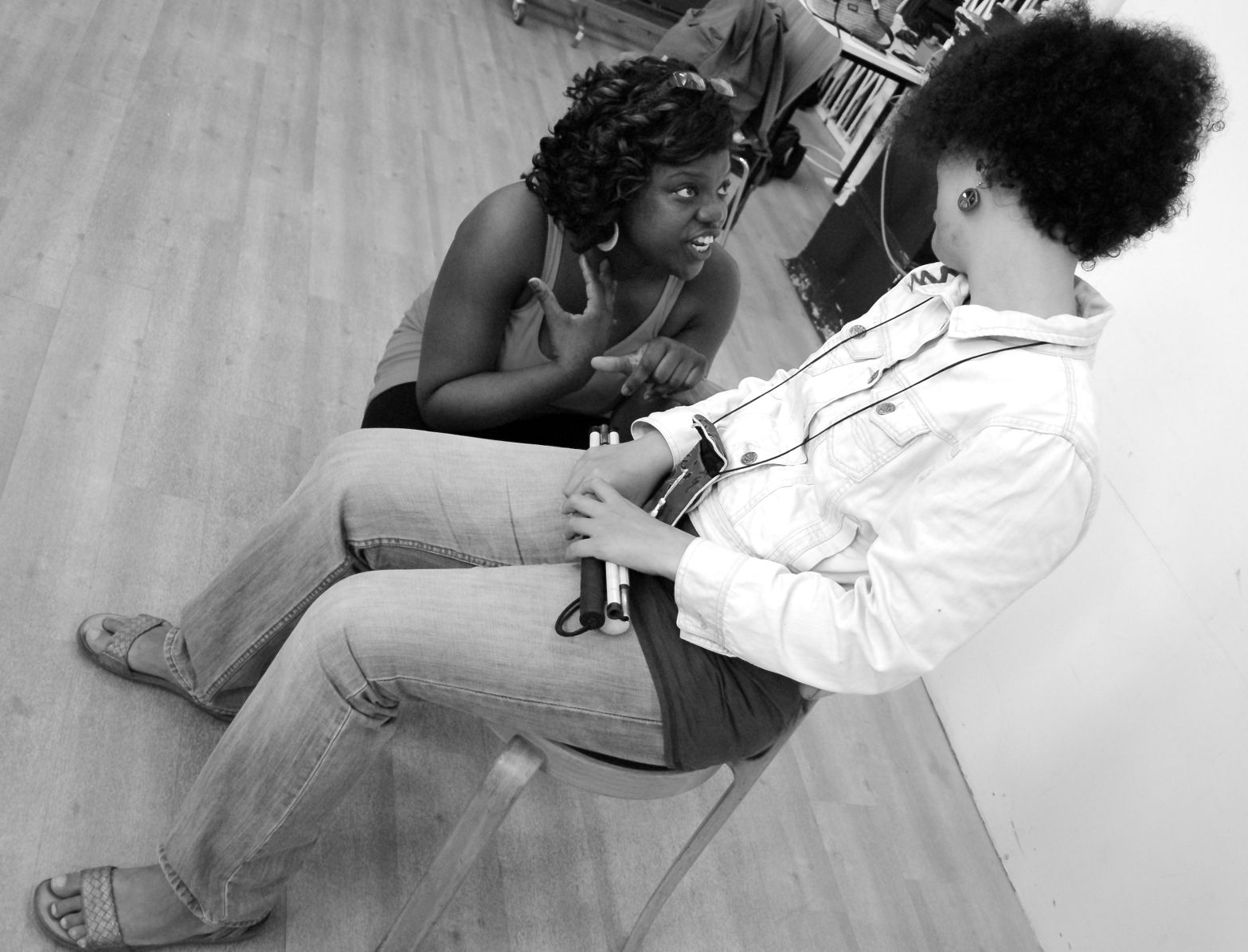 Anita, the assistant facilitator, squats down to talk to one of the participants who is seated looking down at her. Anita's face is animated as she gestures towards herself with one hand. Black and white picture