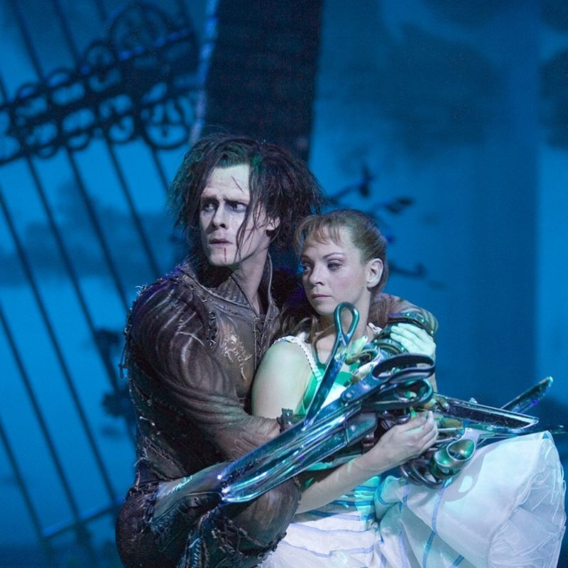 Male dancer dressed as Edward Scissorhands with blade-like fingers hugs a female dancer dressed in white