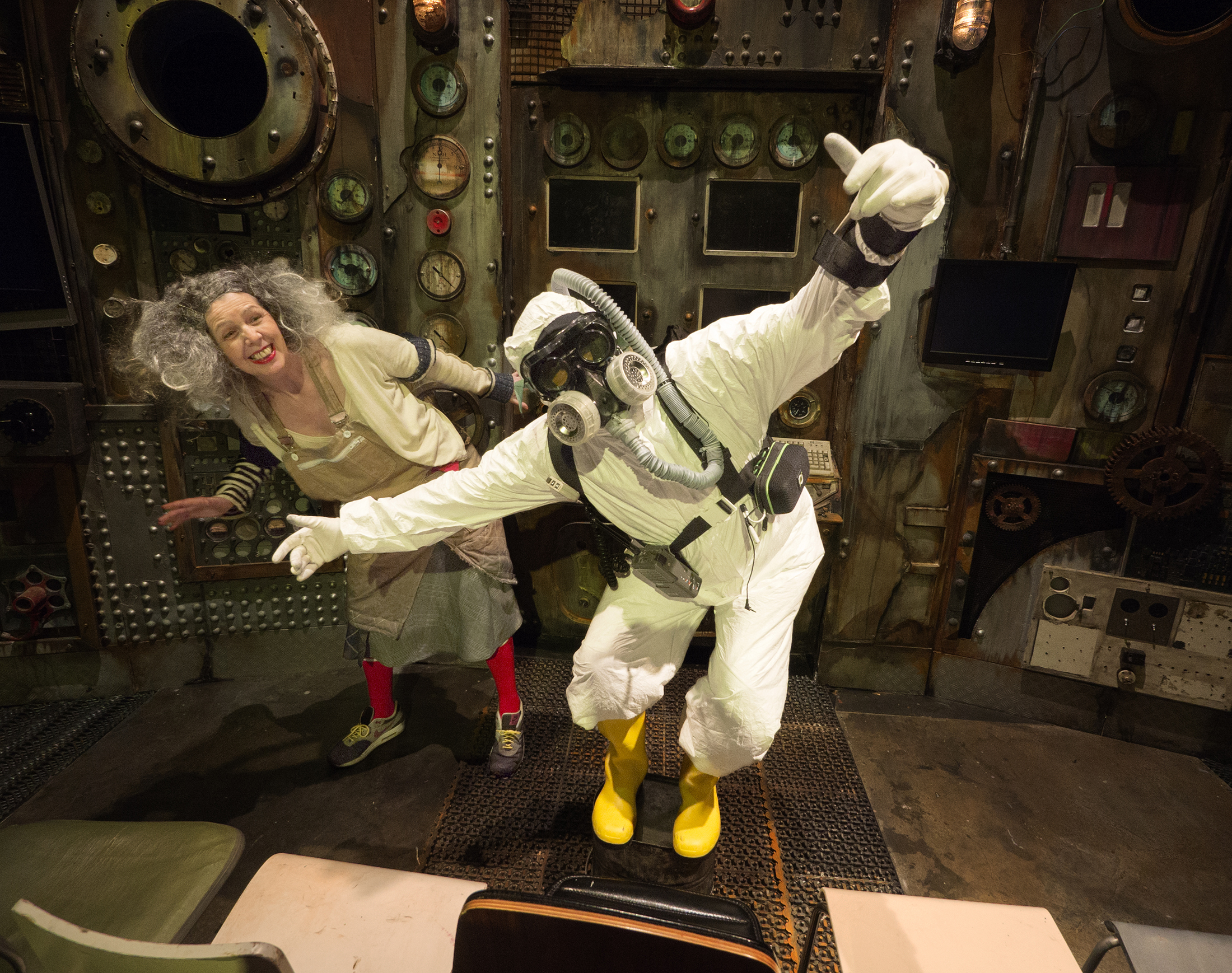 A person in an astronaut costume stands with bent knees and arms wide open while a white woman with curly grey hair peeks from behind in the same stance, smiling