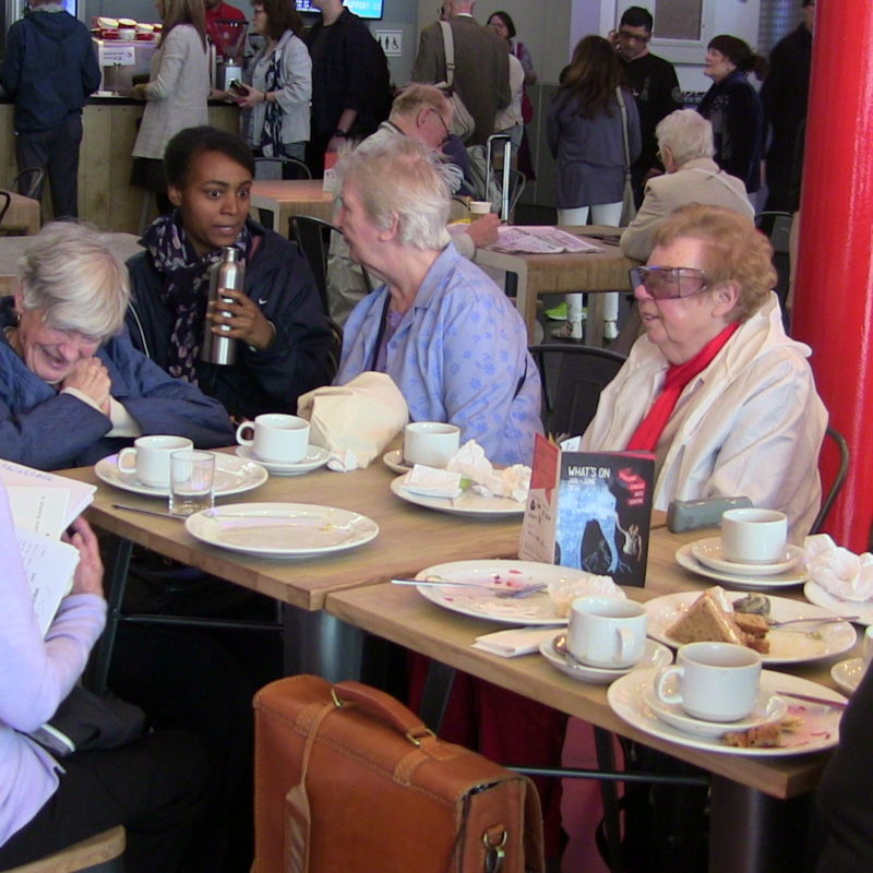A group of older women sit around a table in the foyer at Stratford Arts Centre talking to a younger access worker.