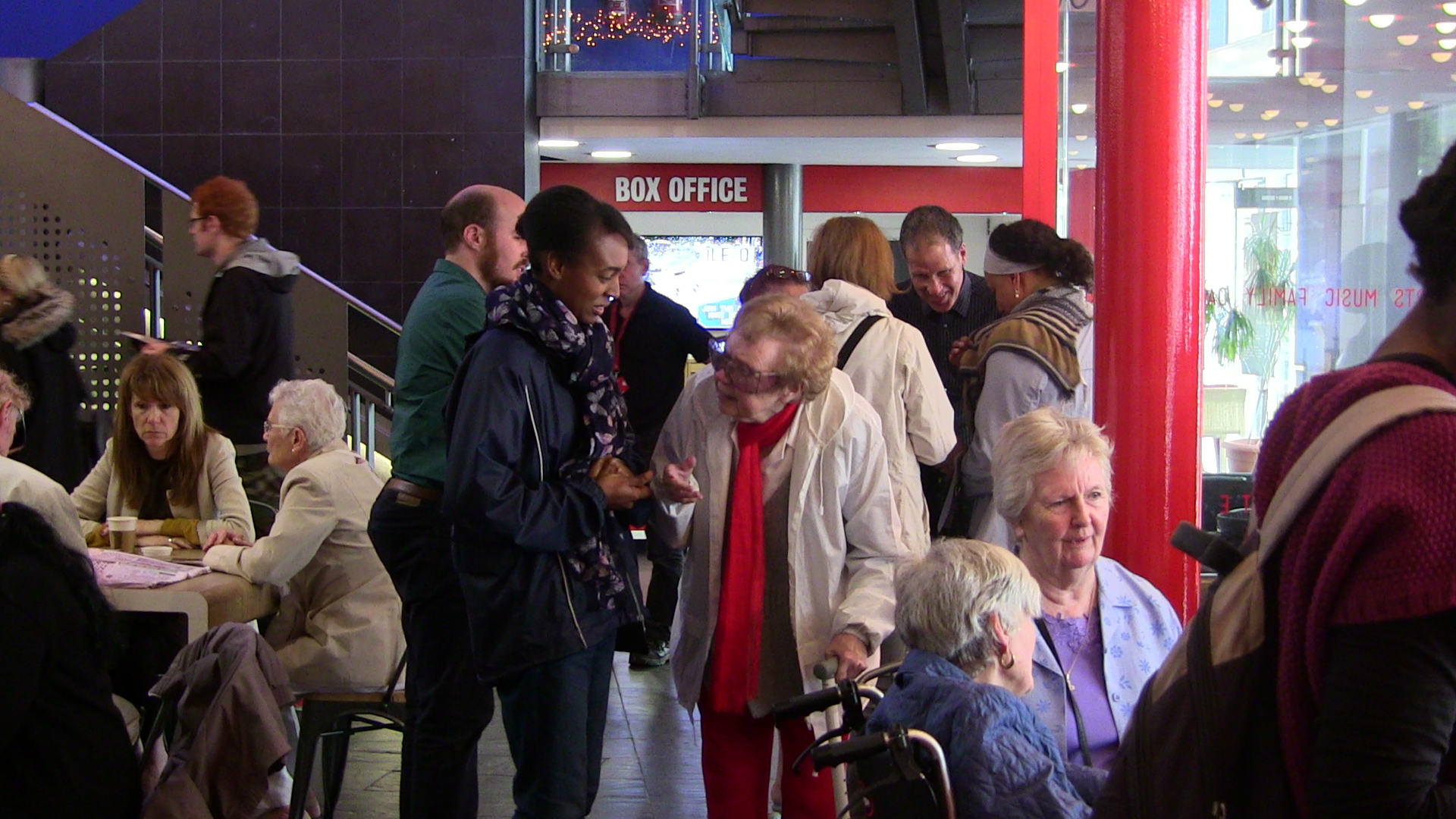 Various groups of people sitting and standing in the Stratford foyer. Centre: an older woman  and access worker in covnersation.