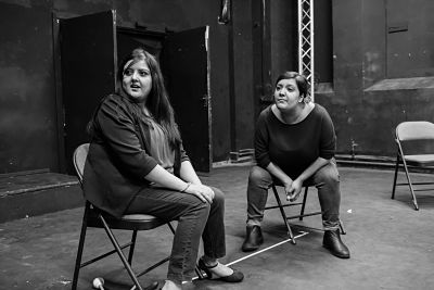 Two youth theatre participants turn to face another (out of shot) with a surprised expression on their faces.