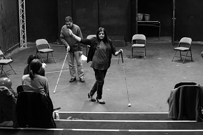 Participants demonstrate movement work with white canes in front of a small audience
