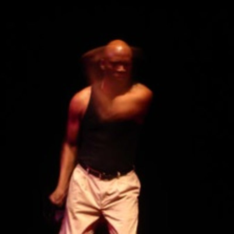 A black male performer standing on stage, his left arm motioning across the stage in a fast blur.