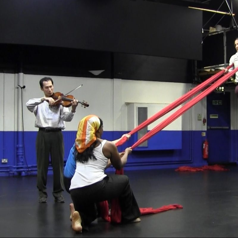 A white female aerialist hangs from two bolts of red silks strung from the ceiling. A Japanese viola player is playing