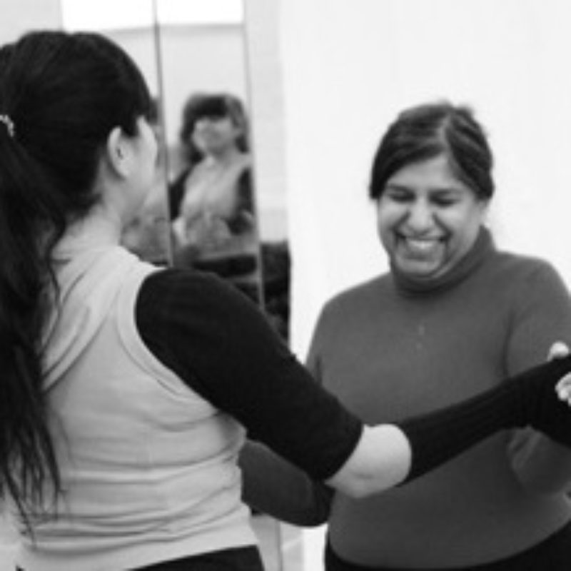 A female dance teacher holds the hands of a smiling dance participant. Black and white image