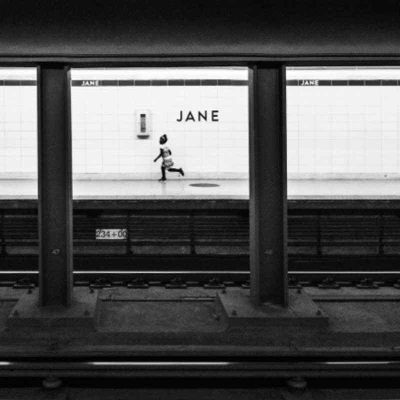 Black and white shot of a young girl running along a deserted station platform