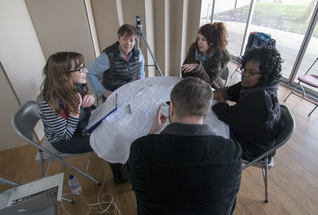 Pic from Flatland project dissemination - group of six people sitting around a table for evaluation and discussion