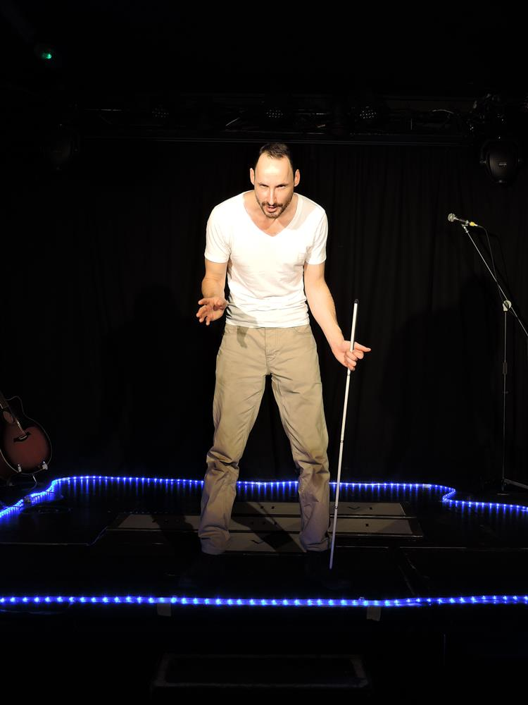 A white male performer stands centre stage