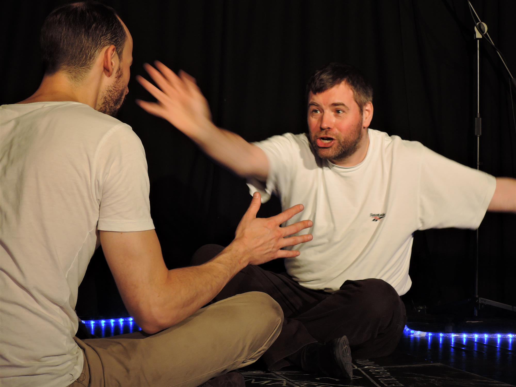 Both performers sat opposite one another in the 'magic circle' onstage. A white man waving his hand in front of the other male performer's face
