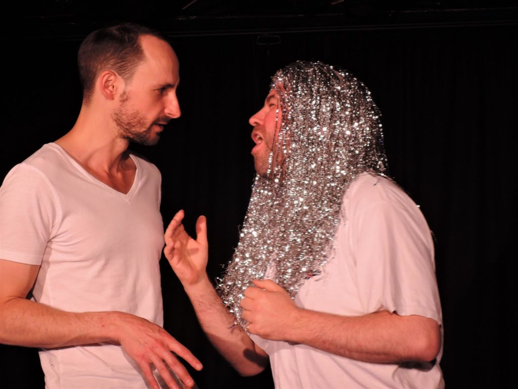 A close up shot of two white men standing facing each other. One wears a long silver tinsel wig and the other looks at him, with a confused expression.