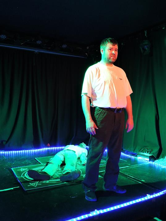 A white male performer stands at the front of the stage in a green light, giving his monologue as the ghost