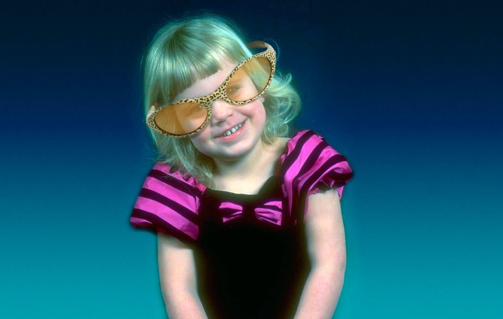 A girl aged 5 or 6 with platinum blonde hair in oversized