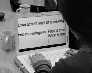 The words of a script can be read on a laptop screen over someone's shoulder in the workshop