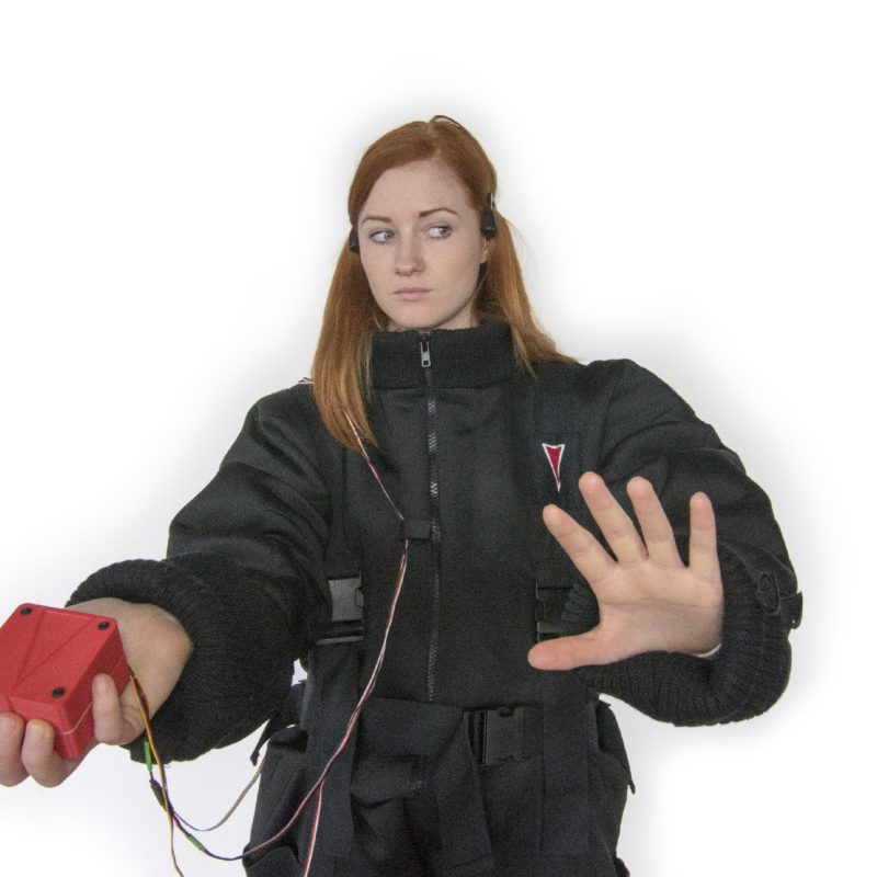 A woman holds a red cube in one hand