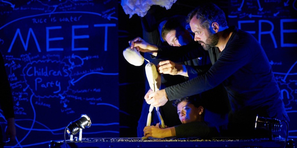 Three puppeteers, in profile facing left, operating a three-foot tall, featureless puppet.