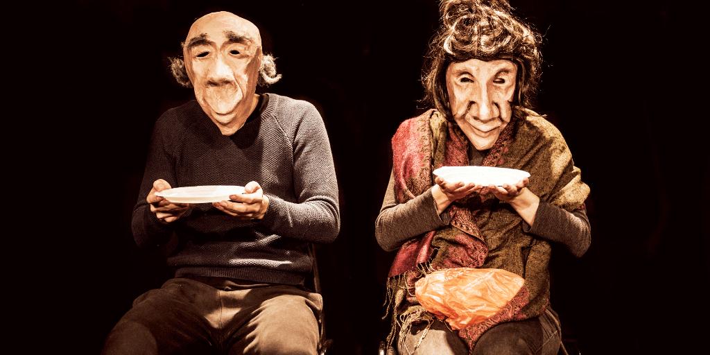 Elderly masked male/female couple sitting side by side holding plates.