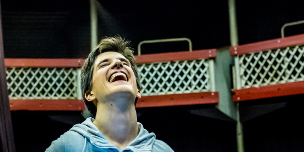 A mid shot of a young woman throwing her head back and laughing. She is onstage in the auditorium of a small-scale theatre.