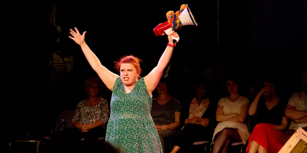 A young woman performing in-the-round. Her arms are raised and she carries a megaphone.