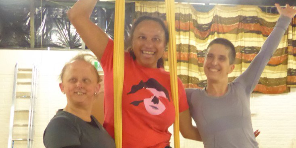A mixed race woman in a red t-shirt supported on yellow aerial silks by two white women. The woman to the left has thin