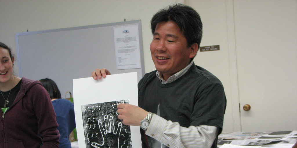 A Japanese man wearing a shirt and green jumper holds up a textured image of a hand.