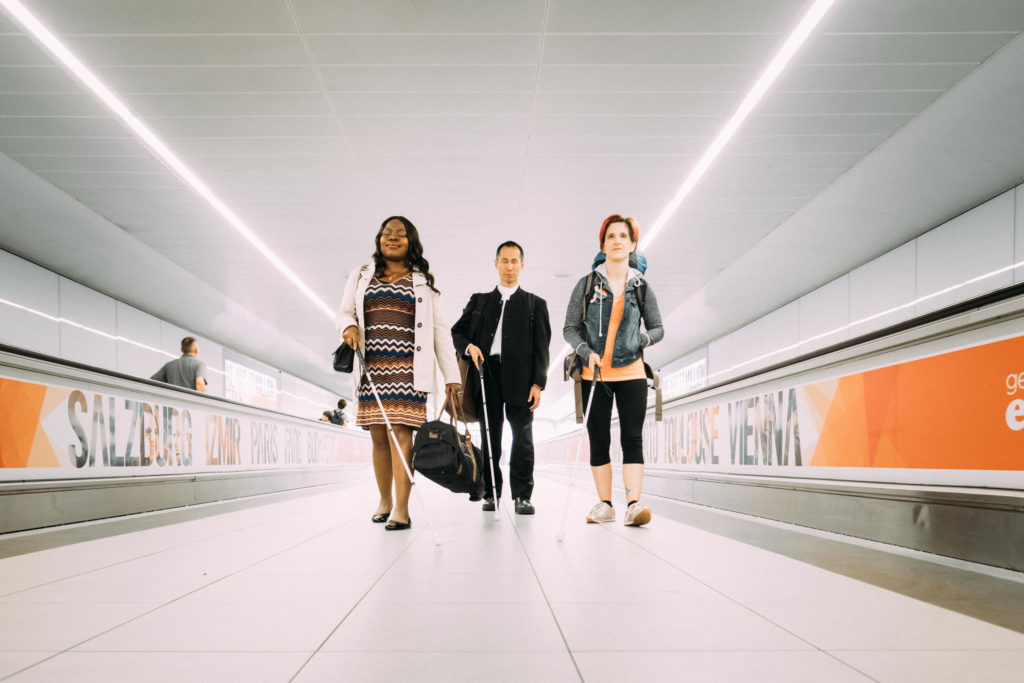 A landscape photo of Victoria, a Nigerian woman, Takashi, a Japanese man and Amelia, an Italian American woman. The three stand in a line, walking towards the camera between two airport moving walkways