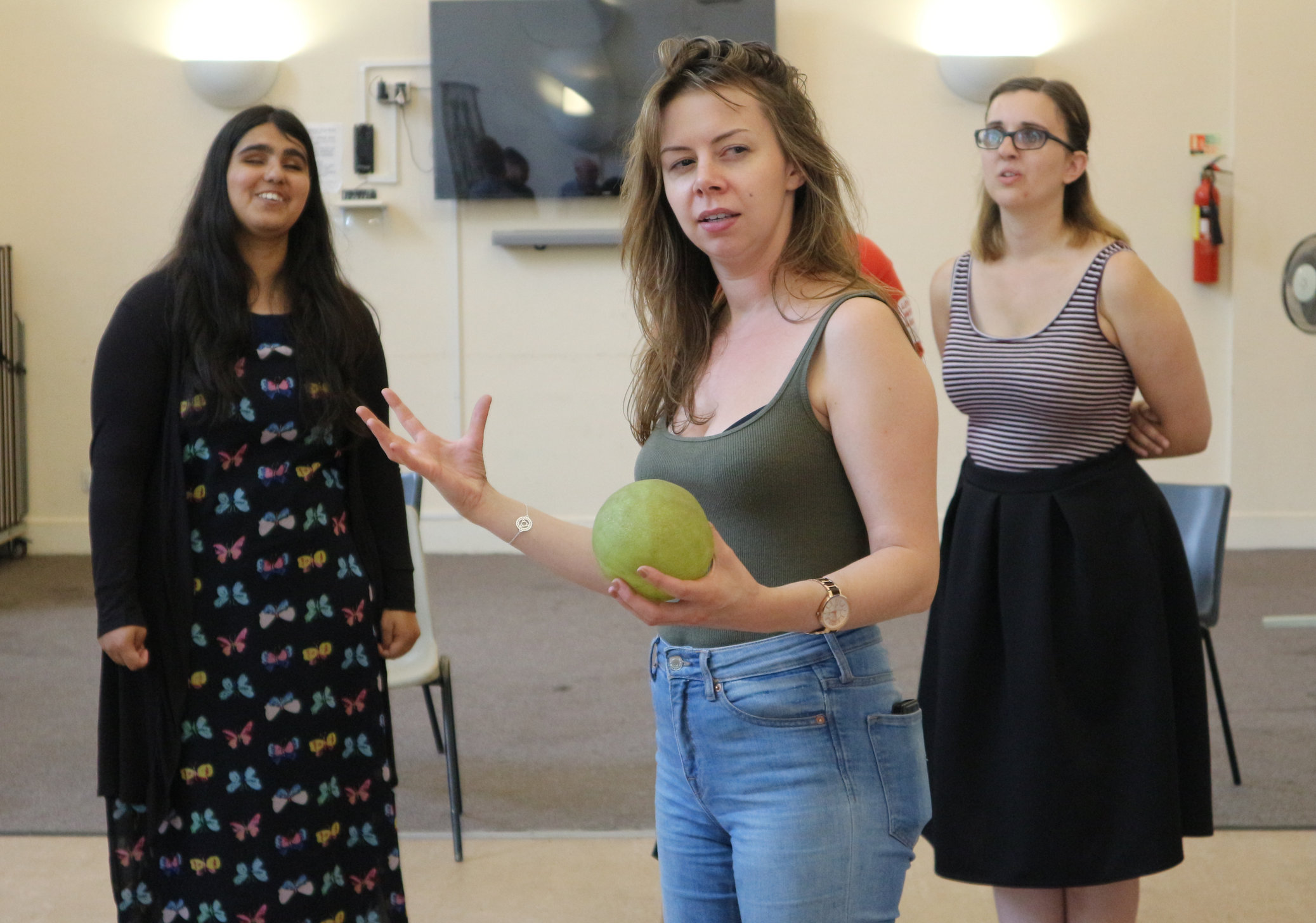 A young woman gesticulating theatrically with one hand and holding up a grapefruit-sized ball with the other.