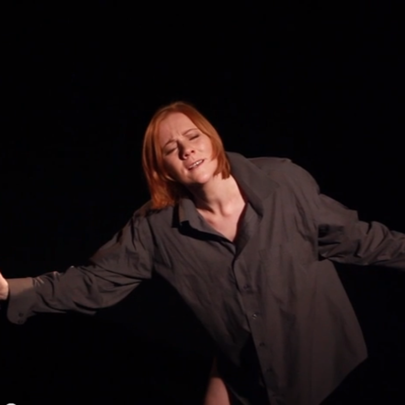 Maggie Tolmie arms outstretched during a monologue