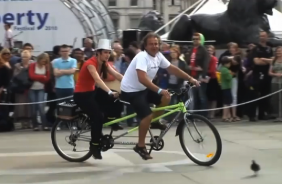 Two performers ride and sing on a tandem