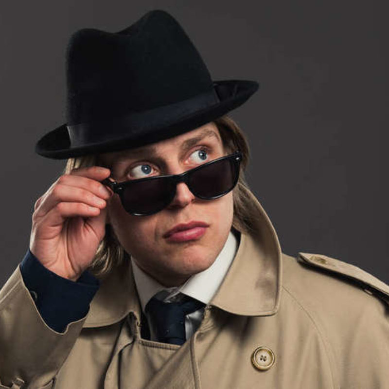 Tom Skelton looking over dark glasses dressed in a beige trench and black trilby