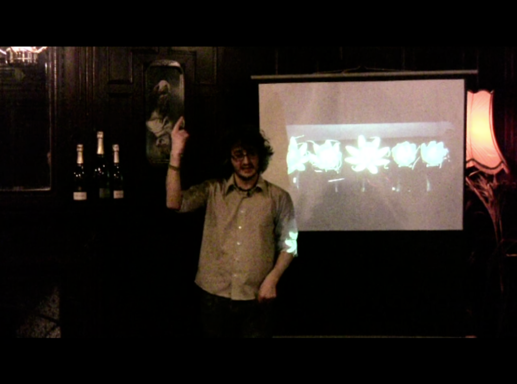White male with glasses speaking in front of a projected photo of the Haptic Lotus Device. Film of a talk about this project