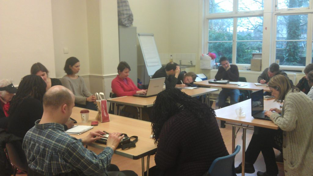 A room of writers working around a table on their scripts
