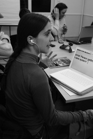 Black and white image of a woman sitting at her laptop (on desk). On the screen is text in large font. She is gesturing with her left hand