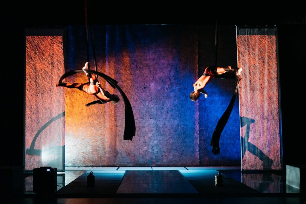 Flight Paths - A wide landscape shot of two women on aerial silks, tumbling through the air mid fall amongst a sea of orange and blue stage lighting.