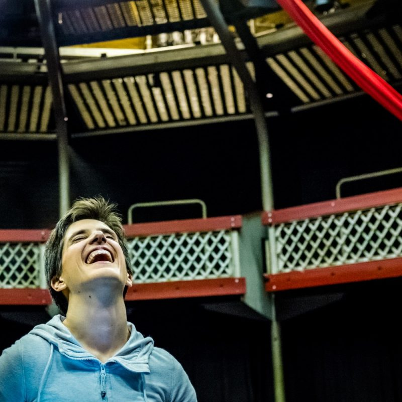 Flight Paths R&D - A medium close up of a woman with cropped hair throwing her head back in laughter. She wears a sky blue, zip up hoodie. She is in a theatre auditorium and aerial silks are visible behind and above her.