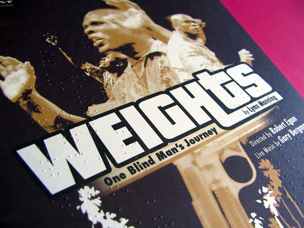 "Weights - An image of a brailed leaflet that reads ""Weights by Lynn Manning"" in big white letters. Behind them stands an African-American man with a shaved head. He holds up his hands, palms facing the front."