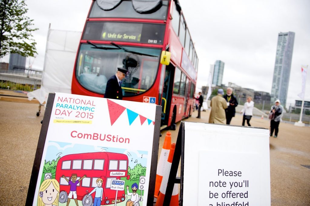 "In the foreground stands a large A board that reads ""National Paralympic Day 2015"" and ComBUStion. Behind the board stands a male bus driver in a peaked, strucutred hat and black jacket with yellow and red buttons. He stands infront of a large red London bus tht reads ""unfit for service"" and is wearing large dark glassess across the front upstairs window."