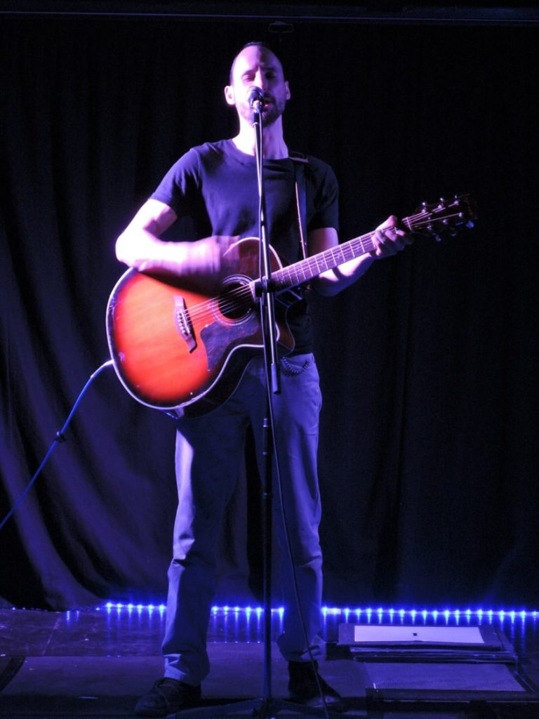 Catching the Ghost - A profile shot of a tall white man with short dark hair and a goatee stands on a dimly lit stage. He sings into a microphone, placed on a stand and strums of a guitar.