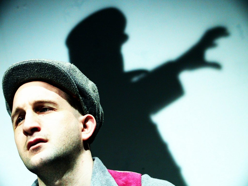 Resistance - Close up of a young man wearing a cap, the shadow of a Nazi officer reaches menacingly in the background