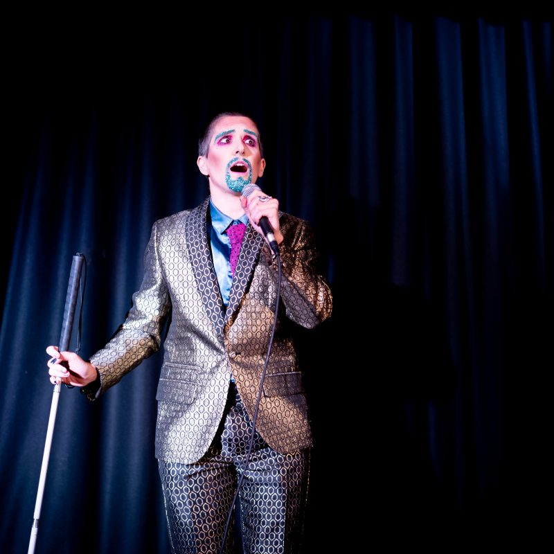 A white drag king wearing a shiny bronze suit, eyes wide, and talking on a microphone