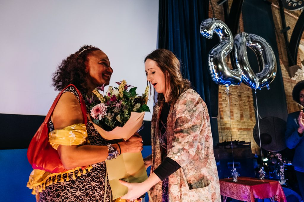 Joanna, a slim white woman with long brown hair hands flowers to Artistic Director Maria Oshodi as they stand smiling in front of a large balloon reading 20