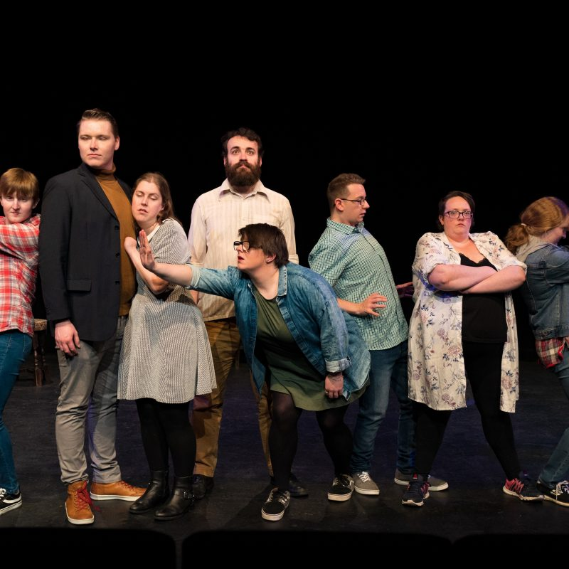 The pathways actors stand together in a line, they stand in an array of poses, arms folded, reaching out, hands on hips and pointing guns fashioned from their hands.