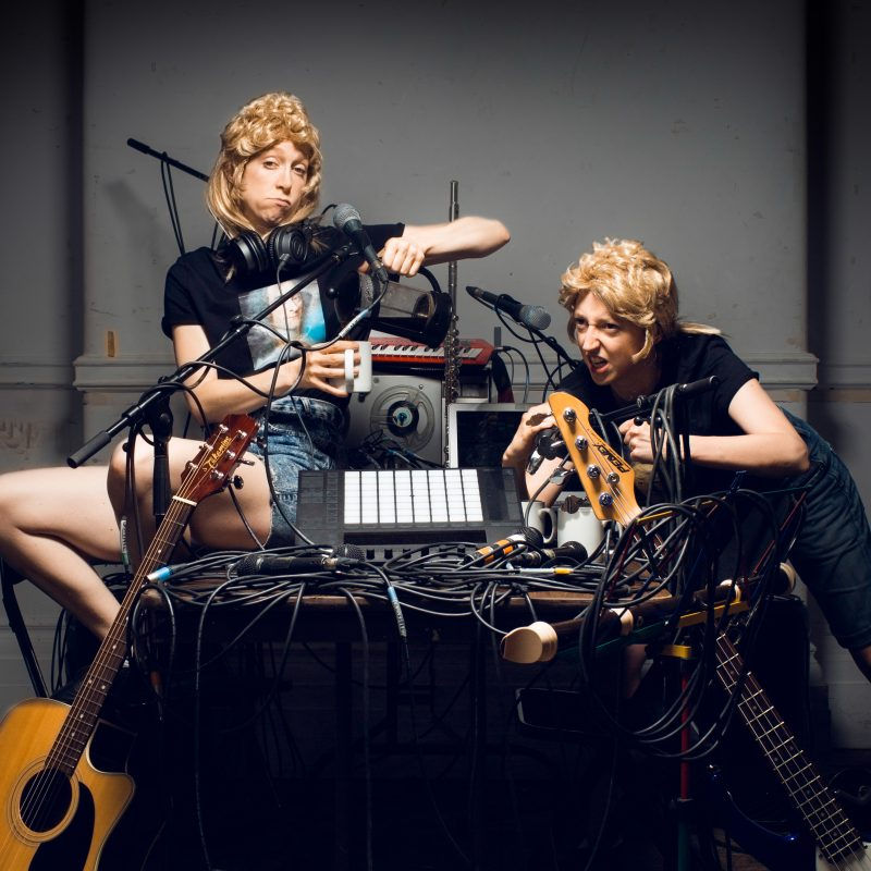 Two white women in blond curly hair pieces perch on a table full of cables entwined with musical instruments and microphones
