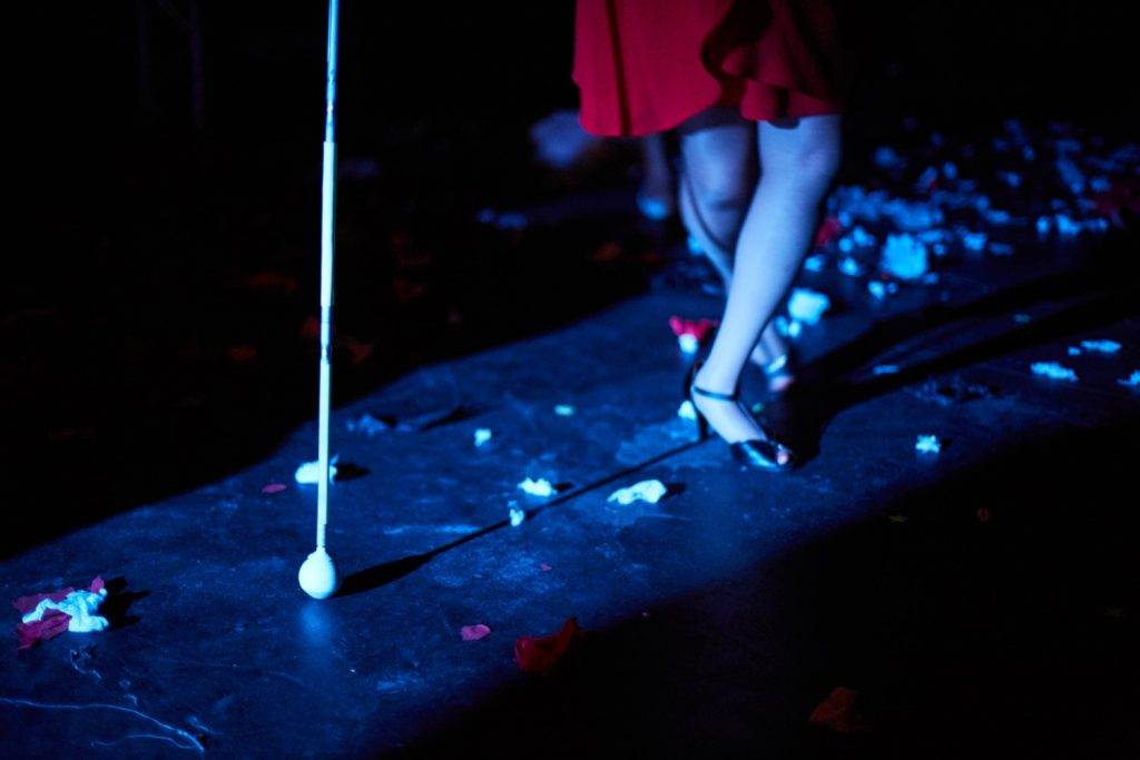 Unexpected - A dimly lit image of two legs wearing black high heeled shoes, crossed over one another, walking towards a white cane which is in the foreground.