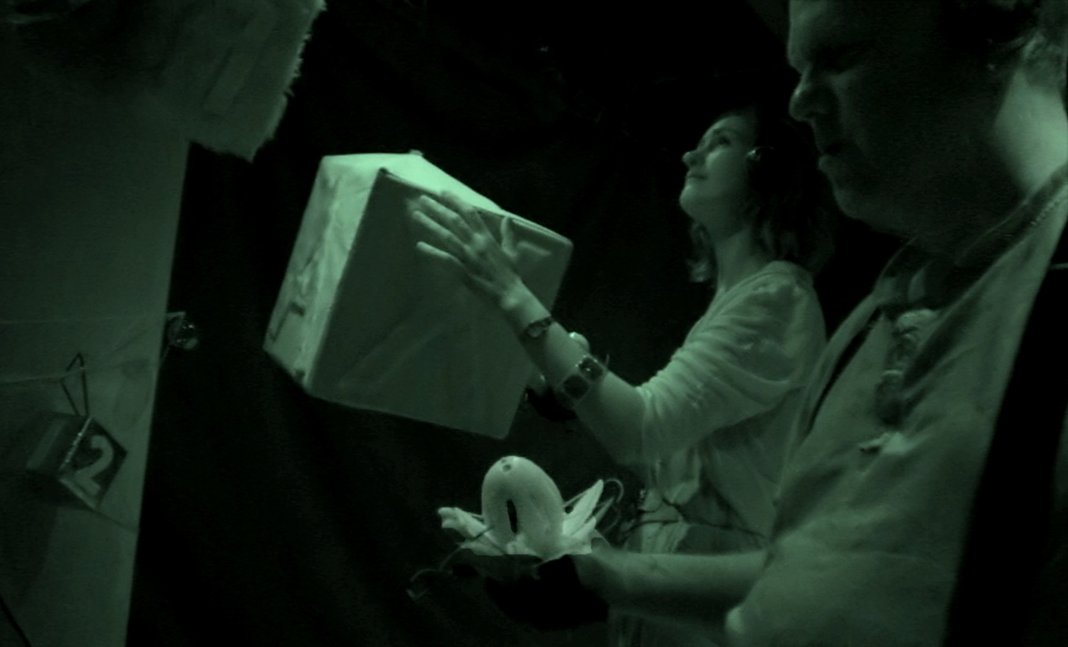 Facing side on to the camera, a woman clutches a large cardbox box. Her face is tilted. A man in the foreground holds a lotus in his hands.