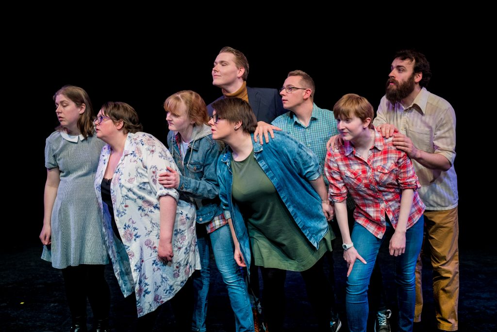 A mixed group of male and female actors stand on stage in a cluster. They are all looking off to their right, leaning in that direction.