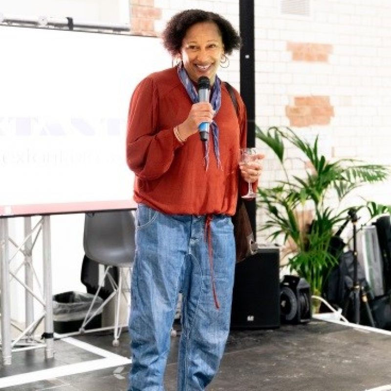 A black woman with short dark, hair, holding a microphone in her left hand and a glass of wine in her right, wearing a red blouse, light blue denim jeans and white boots.