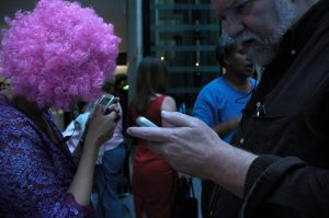 The hands of black woman in a purple dress with matching curly wig, opposite the hands of a white man. They are both holding mobile phones