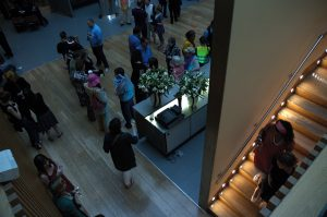 Party guests drinking and chatting on the left, with a woman in a red spotted dressed descending a lit stairwell on the right