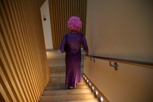 A woman in a long purple dress and matching curly wig descends a lit staircase leading to the party floor